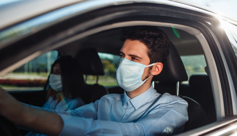 Homem dirigindo carro utilizando máscara