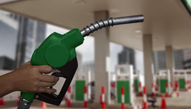 mão com bomba de gasolina ao fundo
