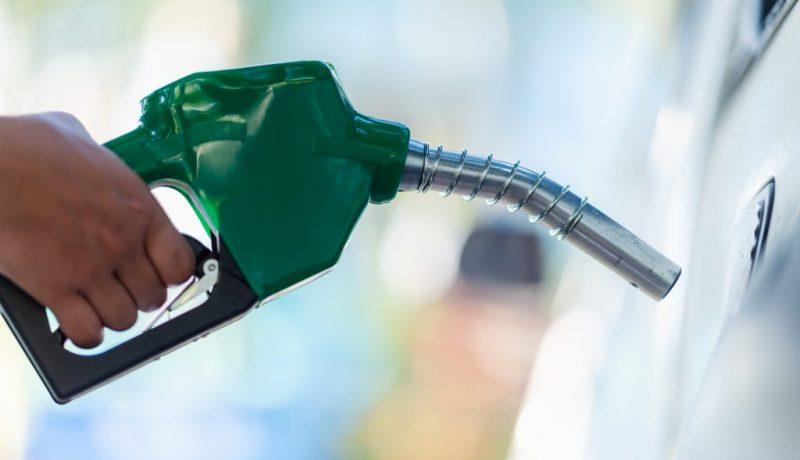 Mão segurando mangueira de gasolina
