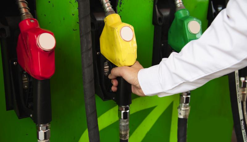 homem segurando mangueira da bomba de gasolina