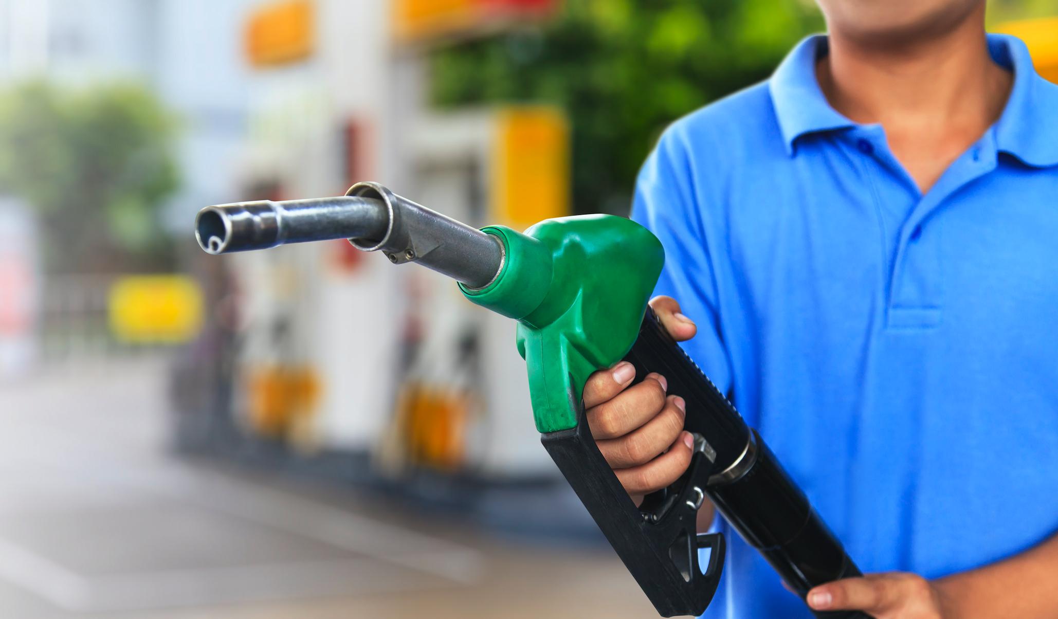 Homem segurando mangueira de gasolina no posto