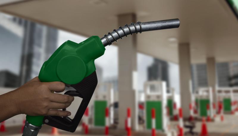 mão segurando mangueira de combustível com posto de gasolina ao fundo